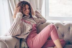 Tonårs- flicka i tröja och jumpsuit på en soffa arkivbilder