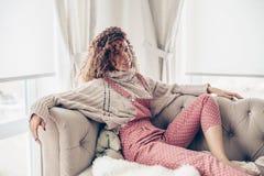 Tonårs- flicka i tröja och jumpsuit på en soffa fotografering för bildbyråer