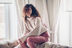 Tonårs- flicka i tröja och jumpsuit på en soffa arkivfoto