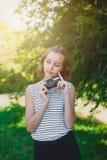 Tonårs- flicka med den retro kameran i parkera Arkivfoto
