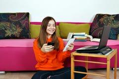 Tonårs- flicka med den smartphoneminnestavlan och bärbara datorn royaltyfri foto