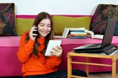 Tonårs- flicka med den smartphoneminnestavlan och bärbara datorn fotografering för bildbyråer
