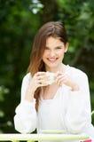 Tonårs- flicka med den varma drinken på det utomhus- kafét royaltyfri bild