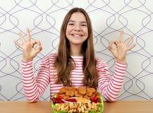 Tonårs- flicka med fega klumpar och det ok handtecknet arkivfoto