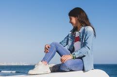 Tonårs- flicka med grov bomullstvillkläder som sitter vända mot medelhavet i spansk kuststad arkivbild