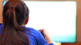Tonårs- flicka med hållande ögonen på tecknade filmer för fjärrkontroll arkivfilmer
