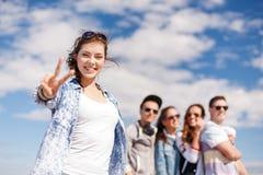 Tonårs- flicka med hörlurar och vänner utanför Arkivfoton
