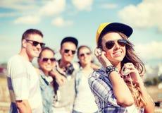 Tonårs- flicka med hörlurar och vänner utanför royaltyfri fotografi