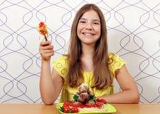 Tonårs- flicka med köttbullar och spagetti för lunch arkivbild