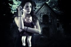 Tonårs- flicka med kniven och dockan framme av ett spökat hus Arkivfoto