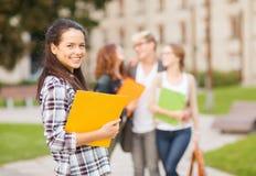 Tonårs- flicka med mappar och kompisar på baksidan Fotografering för Bildbyråer