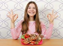 Tonårs- flicka med smörgåsar och ok handtecken fotografering för bildbyråer
