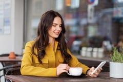 Tonårs- flicka med smartphonen och den varma drinken på kafét royaltyfri fotografi