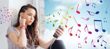 Tonårs- flicka med smartphonen och hörlurar Fotografering för Bildbyråer