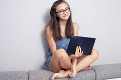 Tonårs- flicka med tableten arkivbilder