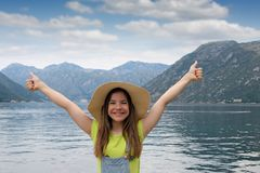 Tonårs- flicka med tummar upp på den semesterKotor fjärden Montenegro royaltyfria bilder