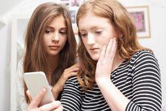 Tonårs- flicka med vännen som trakasseras av textmeddelandet royaltyfria foton