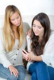 Tonårs- flicka med vännen som trakasseras av textmeddelandet fotografering för bildbyråer