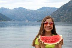 Tonårs- flicka med vattenmelon på en Kotor för sommarsemester fjärd Montenegro fotografering för bildbyråer
