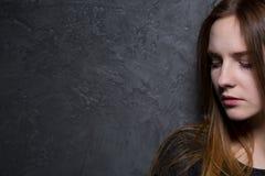 Tonårs- flicka mot den gråa väggen Royaltyfria Foton