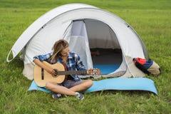 Tonårs- flicka nära tältet som spelar en gitarr Royaltyfri Bild