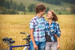 Tonårs- flicka och pojke på en cykel i ett sommarfält av råg Arkivfoto