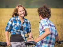 Tonårs- flicka och pojke på en cykel i ett sommarfält av råg Royaltyfria Foton