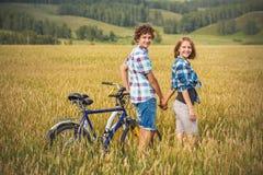 Tonårs- flicka och pojke på en cykel i ett sommarfält av råg Fotografering för Bildbyråer