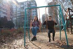 Tonårs- flicka och pojke på gungan Arkivfoton