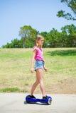 Tonårs- flicka på blå hoverboard Arkivfoton