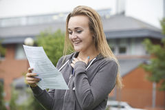 Tonårs- flicka som är lycklig med bra examenresultat Arkivfoto