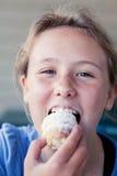 Tonårs- flicka som äter en söt bakelse Royaltyfri Fotografi