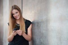Tonårs- flicka som använder den smarta telefonen Royaltyfria Bilder