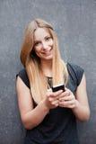 Tonårs- flicka som använder den smarta telefonen Arkivbild