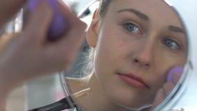 Tonårs- flicka som applicerar fundamentet med svampen, sminkrutin, anletehobby stock video