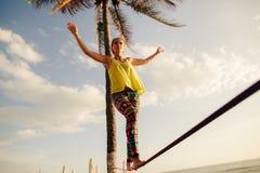 Tonårs- flicka som balanserar på slackline med himmelsikt Royaltyfria Foton