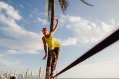 Tonårs- flicka som balanserar på slackline med himmelsikt Arkivbilder