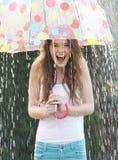 Tonårs- flicka som beskyddar från regn under paraplyet royaltyfria foton