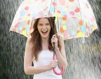 Tonårs- flicka som beskyddar från regn under paraplyet fotografering för bildbyråer
