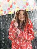 Tonårs- flicka som beskyddar från regn under paraplyet arkivbild
