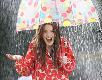 Tonårs- flicka som beskyddar från regn under paraplyet Arkivbilder