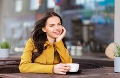 Tonårs- flicka som dricker varm choklad på stadskafét royaltyfria bilder