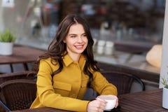 Tonårs- flicka som dricker varm choklad på stadskafét arkivbild