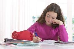 Tonårs- flicka som gör läxa för skola arkivbild