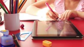 Tonårs- flicka som gör läxa på minnestavladatoren arkivfilmer