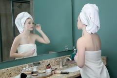 Tonårs- flicka som gör makeup Arkivfoton