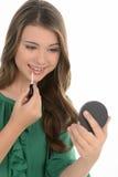 Tonårs- flicka som gör smink. Gladlynt tonårs- flicka som gör smink Fotografering för Bildbyråer