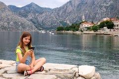 Tonårs- flicka som har gyckel med den smarta telefonen på semester royaltyfria foton