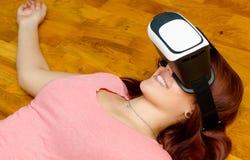 Tonårs- flicka som har gyckel med virtuell verklighet genom att använda hörlurar med mikrofon för vr 3d Fotografering för Bildbyråer