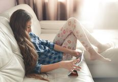 Tonårs- flicka som hemma sitter med en minnestavlaPC Livsstilbild av den härliga Caucasian långhåriga flickan arkivbild